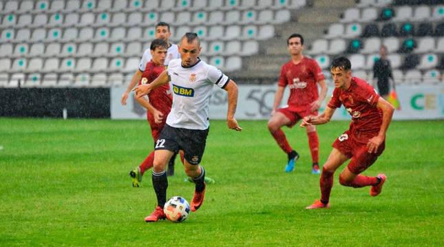 Madrazo conduce el balón ante la presión de Aimar Oroz.