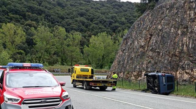 Lugar del accidente con el automóvil volcado y una patrulla de la Policía Foral atendiendo el suceso.