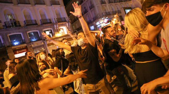 Jóvenes en Madrid celebran el final del toque de queda en la Puerta del Sol.