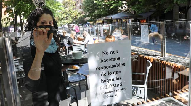 Filipa Oliveira, la propietaria, junto al cartel en el que alerta a sus clientes.