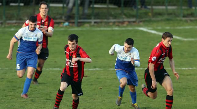 Foto de Patxi Iturralde conduce el balón en una contra mientras su compañero Asier Lasanta le acompaña. Detrás, jugadores del Burladés B.