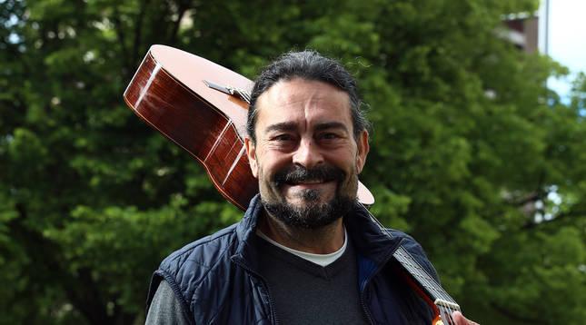 Chicho Sanz Nicuesa cerca de su lugar de trabajo, en Pamplona, con la guitarra al hombro.