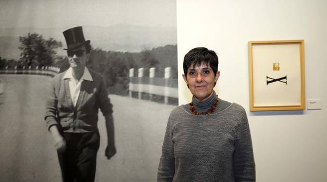 Glòria Bordons, comisaria de la exposición, junto a una fotografía de Joan Brossa.