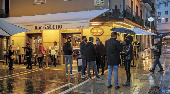 Viandantes y clientes tomando algo en la terraza del bar Gaucho, en Pamplona, en la lluviosa noche del pasado jueves.