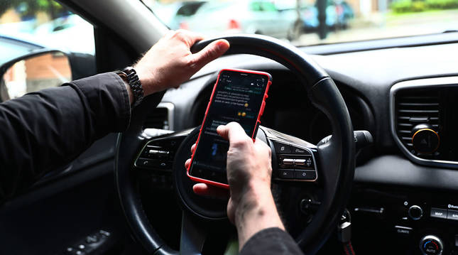 Un conductor lee y escribe mensajes en su teléfono, mientras sostiene el volante de su vehículo.