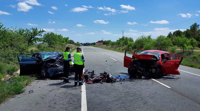 Dos agentes de la Guardia Civil junto a los vehículos implicados en el accidente.