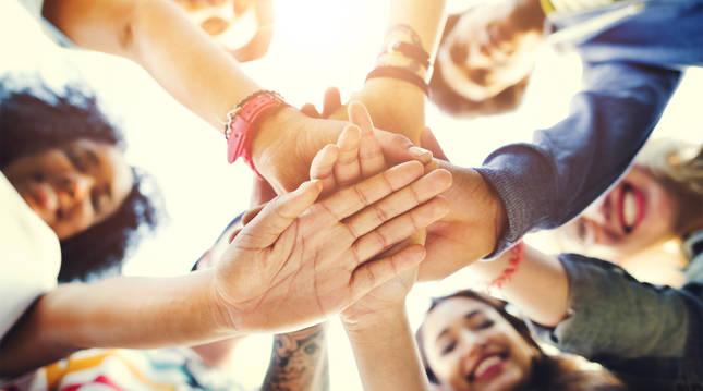 Varios jóvenes enlazan las manos.