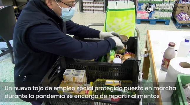 Un voluntario ordena comda en una caja para repatrir a las familias en exclusión social.
