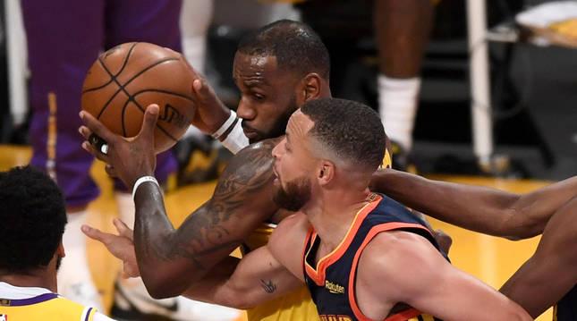 LeBron James cubre el balón ante la defensa de Stephen Curry.