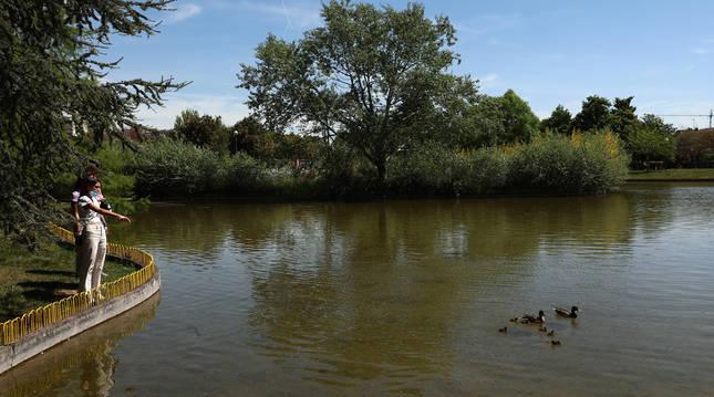 Una pareja de jóvenes observa a una familia de patos en el lago de Barañáin.