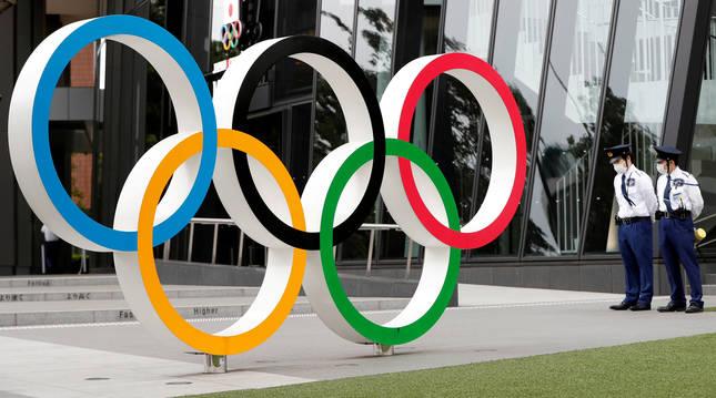 Dos guardias de seguridad junto al embnlema olímpico en la oficina de la organización de los JJ OO de Tokyo en la capital nipona.