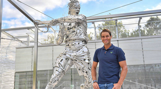 Rafa Nadal posa junto a su estatua.