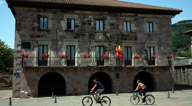 Dos personas atraviesan en bici la plaza de los Fueros, con el Ayuntamiento al fondo.