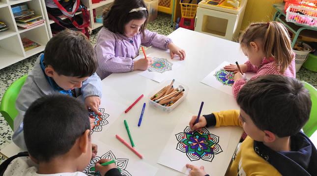 Un grupo de niños comienza a colorear en el aula los dibujos que luego completaron los mayores.