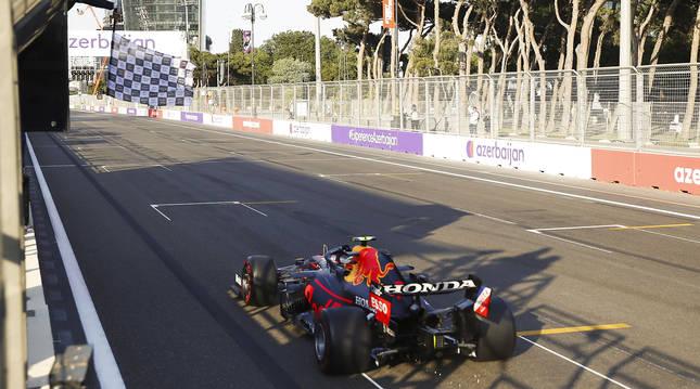 'Checo' Pérez recibe el banderazo a cuadros tras cruzar la línea de meta en primera posición en el circuito de Baku.