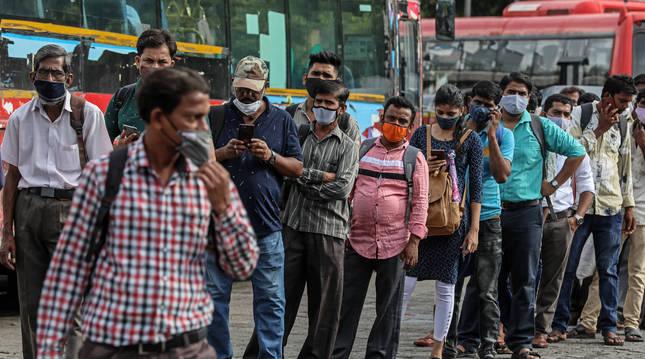 Varias personas, protegidas con mascarillas, esperan al autobús en Mumbai (India).