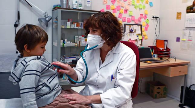 La enfermera Arantxa Arellano, con Xuban, de 3 años, en su consulta de la Ikastola San Fermín.