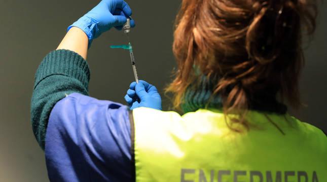 Una enfermera, preparando una vacuna en Refena.