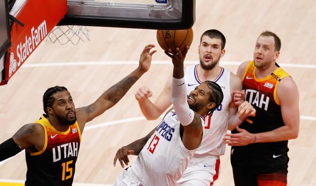 El escolta de Los Angeles Clippers Paul George conduce el balón al aro contra Derrick Favors de Utah Jazz.