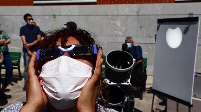 Una persona contempla el eclipse de sol de este jueves desde el Planetario de Pamplona.
