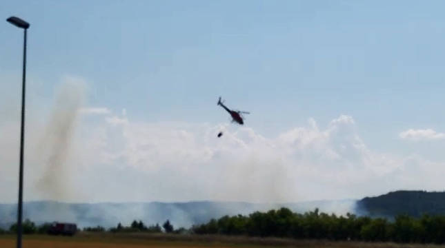 Un helicóptero rocía con agua la zona afectada por las llamas.