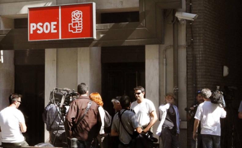 Numeros medios de comunicación permanecen en la entrada de la sede en Madrid del PSOE.