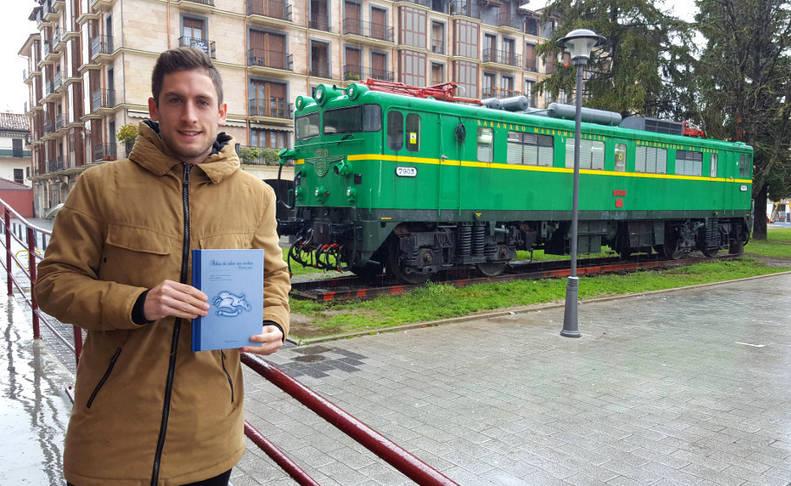 El alsasuarra Ander Claver Goikoetxea, coautor de 'Atlas de islas sin coches', junto a la locomotora instalada en el centro de Alsasua.