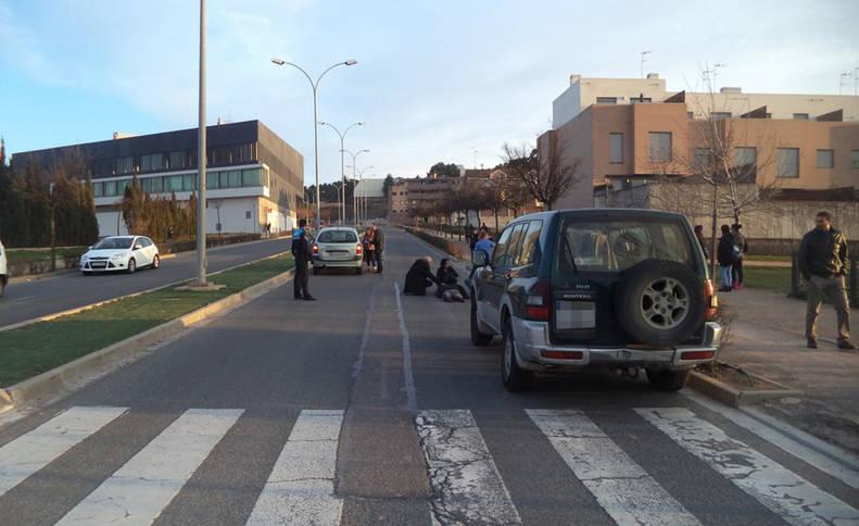 Dos personas atienden al hombre, tendido en el suelo, tras ser atropellado en el paso de cebra. A la izquierda, el coche que causó el accidente.