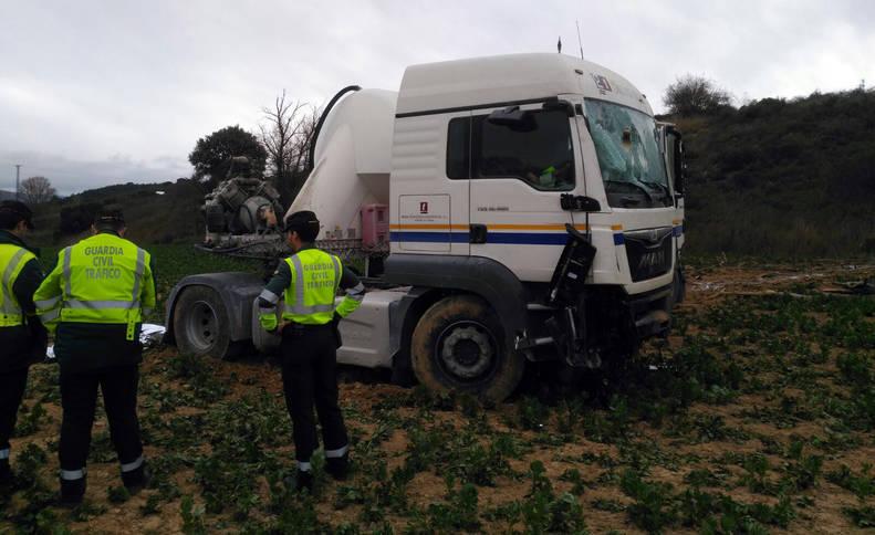 Imagen del camión accidentado junto a varios agentes de la Guardia Civil.