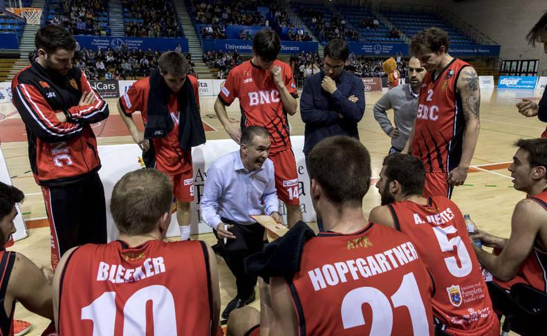 Los jugadores del Basket Navarra atienden a su entrenador durante un partido en el Pabellón Universitario