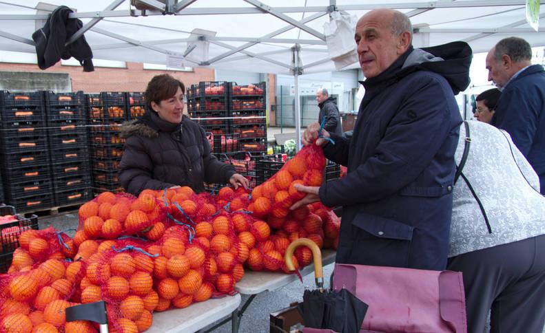 Rebeca Luque, que lleva siete años en el mercadillo, vende naranjas a unos clientes.