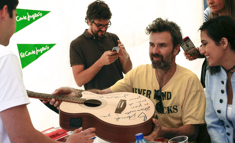 Pau Donés firma una guitarra en las Ramblas de Barcelona, durante la tradicional fiesta de Sant Jordi