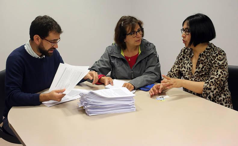 Foto de David Navarro, Claudia Pérez y Nuvia Fuertes, médicos de familia eventuales en Navarra. En el centro, la pila de contratos firmados por uno de ellos.