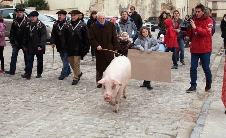 Jesús Casamayor conduce el cerdo junto a sus nietas y a varios representantes de la orden del Cuto Divino de Tafalla, el pasado año. En la presente edición, Casamayor delega sus funciones después de varios años.