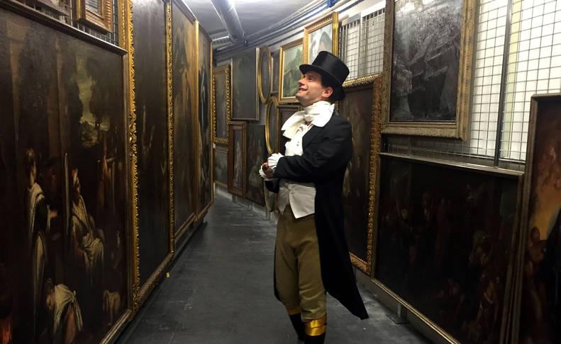 """Un actor caracterizado como el """"Marqués de San Adrián"""" contempla algunas de las obras conservadas en el renovado sótano del Museo."""