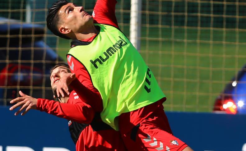 Luis Perea coge impulso en busca del balón junto a Roberto Torres, este jueves en Tajonar.