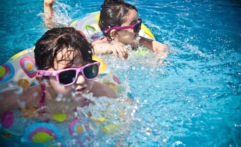 Dos niñas juegan en la piscina de una casa rural