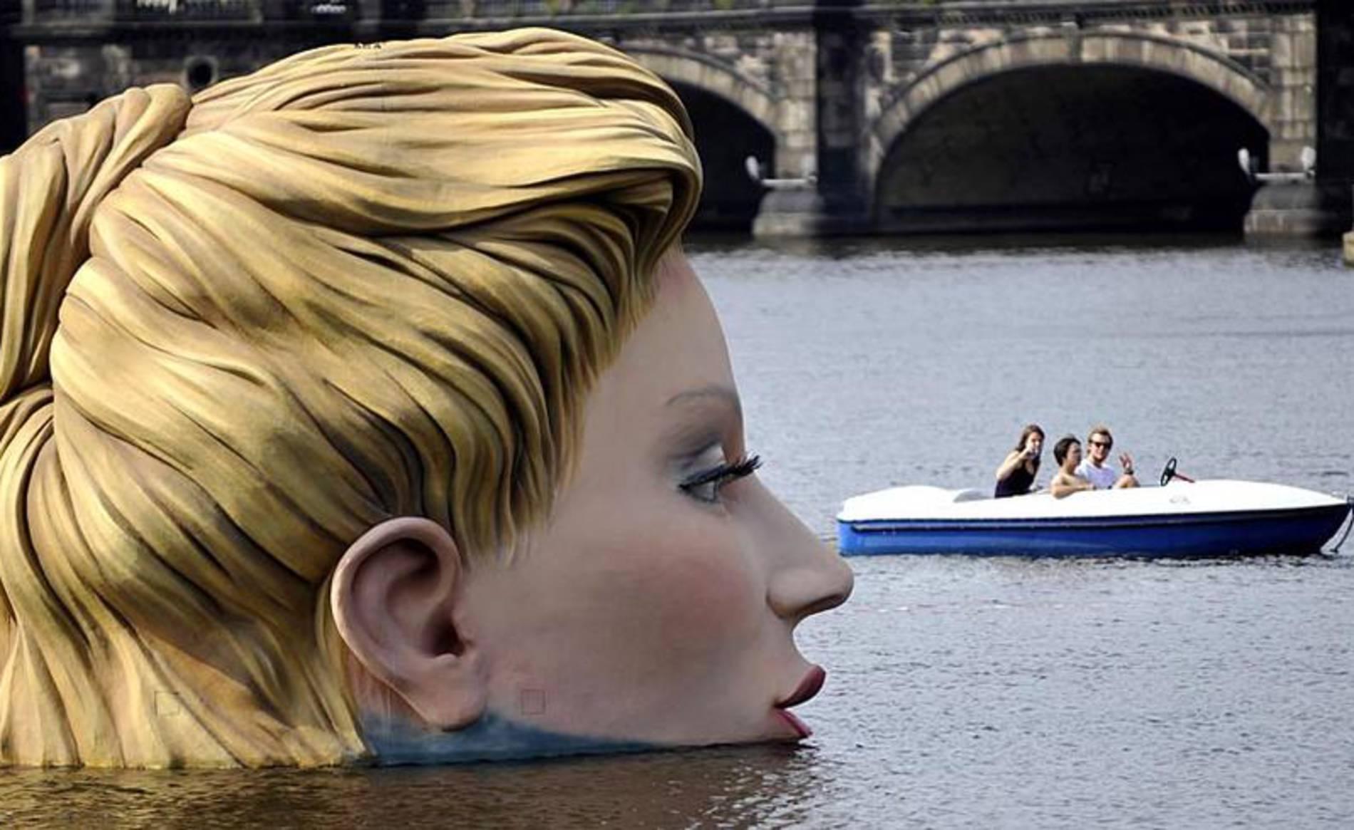Gente en un bote mira a la escultura de una sirena en el lago Alster en Hamburgo.
