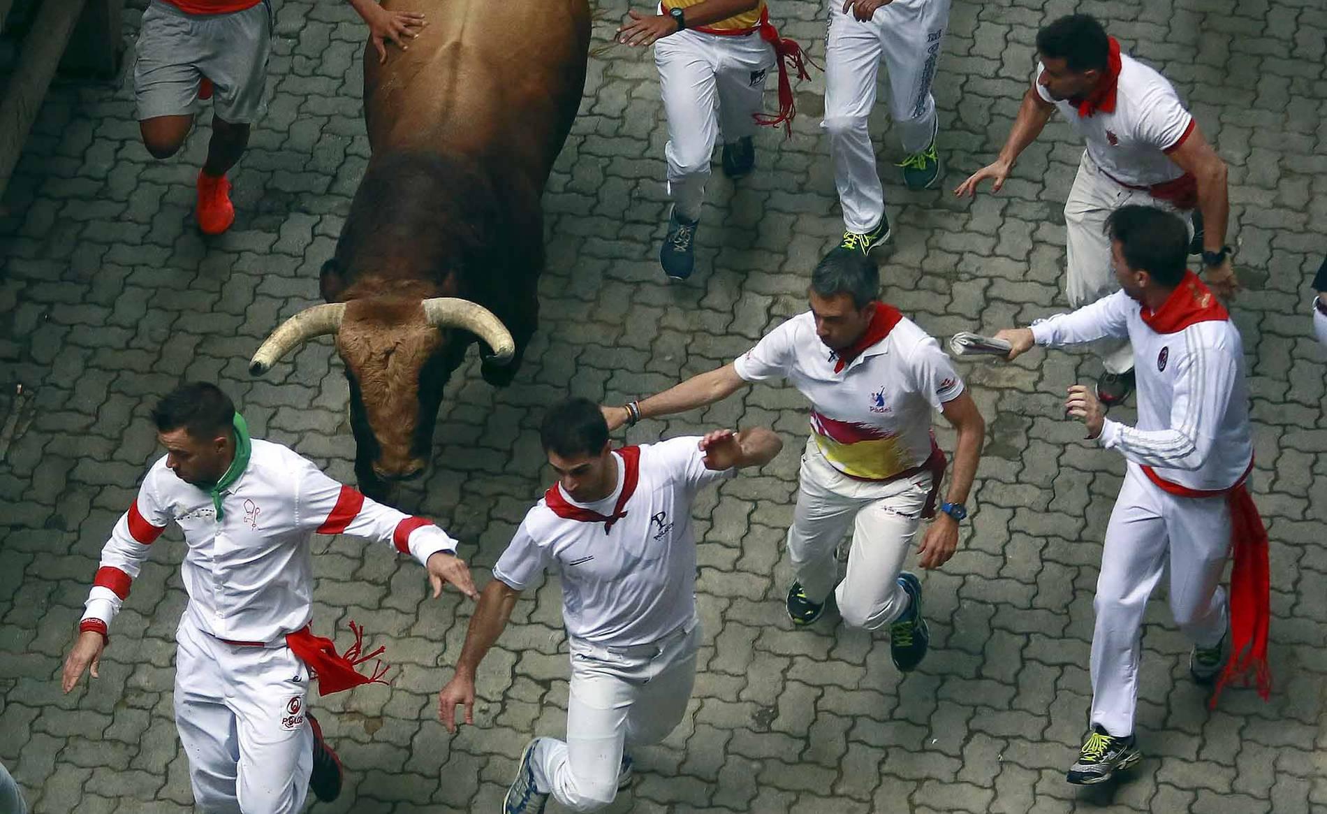 Joven enganchado por un toro a la entrada de la plaza de toros (1/12) - Imágenes del tercer encierro Sanfermines 2017. - San Fermín -