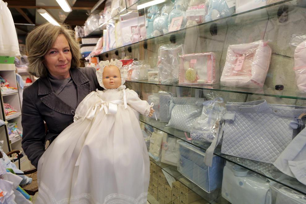 96c5dce90 Ana Moreno Abaurrea sujeta en brazos a un muñeco vestido con un faldón de  bautizo en el interior de su tienda