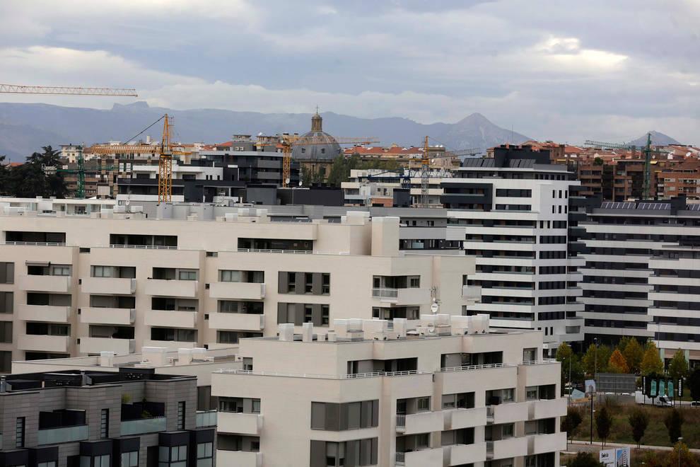 Foto, en primer plano, de viviendas del barrio pamplonés de Lezkairu; al fondo, el Ensanche.