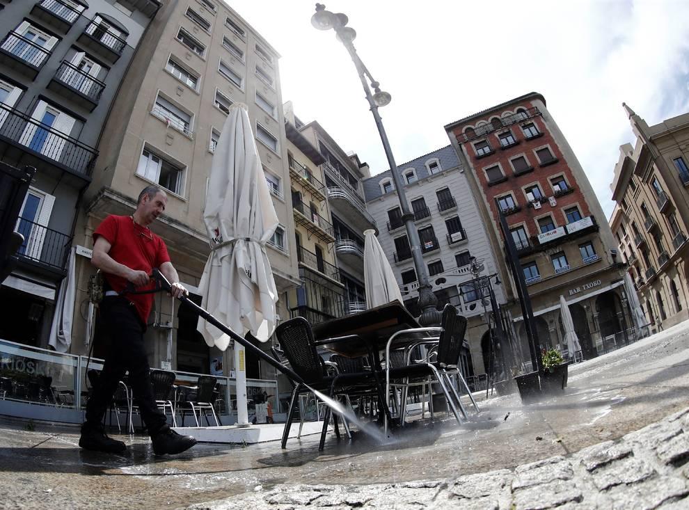 El dueño de un bar de la Plaza del Castillo desinfecta su terraza.