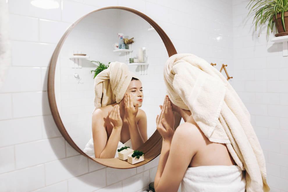 Imagen de una joven que se realiza una limpieza facial frente a un espejo.