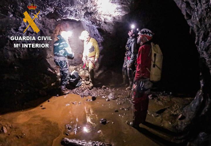 Guardia Civil y los espeleólogos, junto a la bolsa de explosivos en el interior de la cueva.