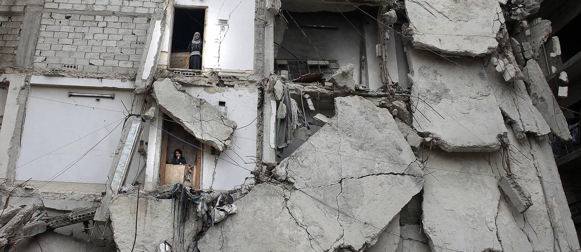 Foto de 13 de febrero de 2020. Dos vecinas se asoman por las puertas de sus casas en el edificio en el que viven en Ghouta, Damasco