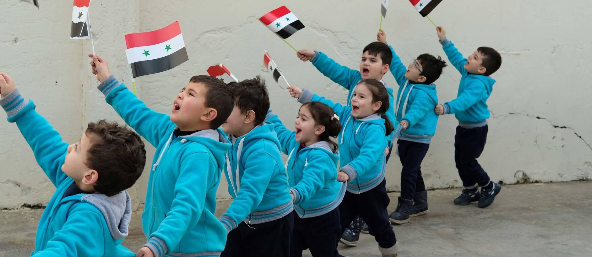 Niños del centro de los Maristas Azules ondean banderas sirias de camino a los microbuses que les van a llevar a visitar la parte de la ciudad después de ocho años ocupada por los rebeldes.