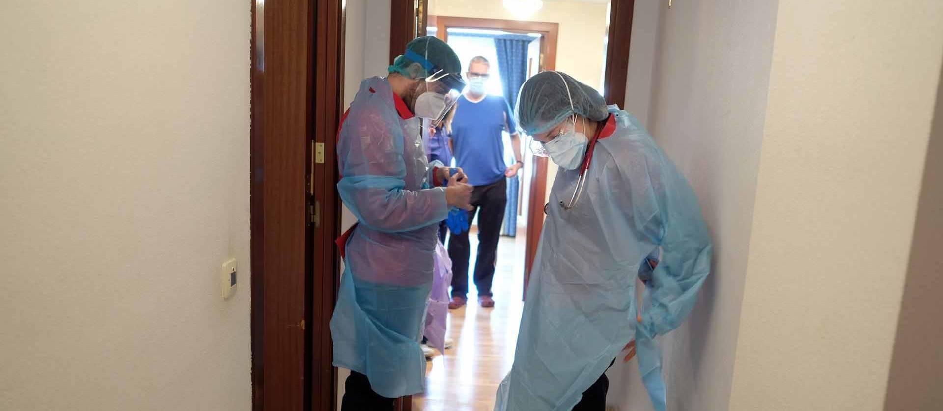 Foto de María Hidalgo, internista, y David García, enfermero, se preparan en el rellano de la casa de un paciente con covid antes de entrar.